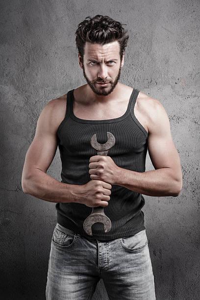 Schöne grobe Mann hält ein Schraubenschlüssel über eine strukturierte Hintergrund – Foto