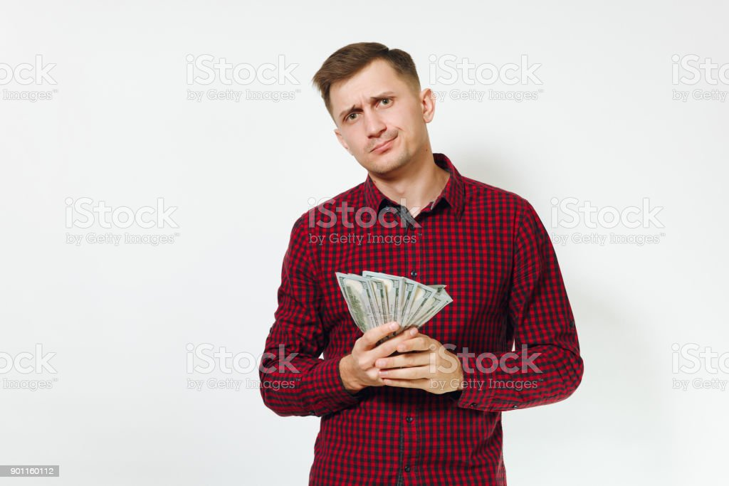 fc48110b Handsome sad confused annoyed crying caucasian young business man in red  shirt holding few banknotes money