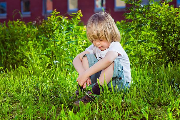 Schöne traurige kleine Junge sitzt auf Gras in der Nähe von seiner Schule – Foto