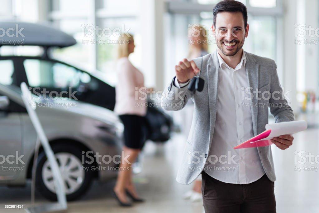 Handsome salesman at car dealership selling vehichles stock photo