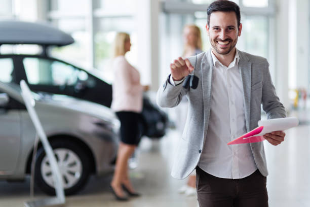 Handsome salesman at car dealership selling vehichles Handsome young salesman at car dealership selling vehichles car salesperson stock pictures, royalty-free photos & images