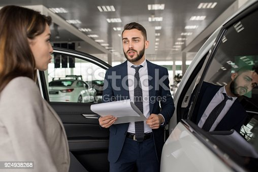 939005154 istock photo Handsome Salesman Selling Cars in Showroom 924938268