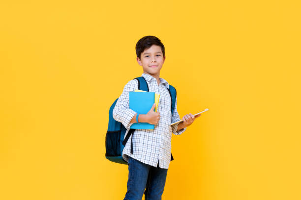 Handsome schoolboy with backpack holding books and tablet computer stock photo