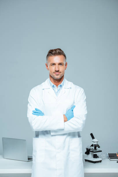 handsome scientist in white coat and latex gloves standing with crossed arms and looking at camera isolated on white - лабораторный халат стоковые фото и изображения