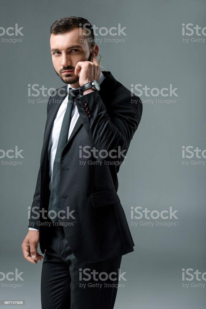 Mensaje escucha guapo guardia de seguridad con seguridad auricular y mirando lejos aislado en gris - foto de stock