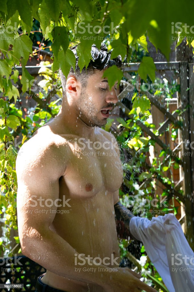 Handsome semi naked man with muscles and bare chest caught in shower of rain in garden stock photo