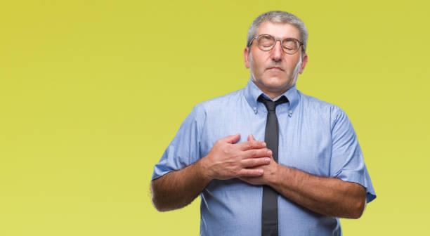 hübsche ältere geschäftsmann über isolierten hintergrund lächelnd mit händen auf der brust mit geschlossenen augen und dankbare geste im gesicht. gesundheitskonzept. - die wahrheit tut weh stock-fotos und bilder