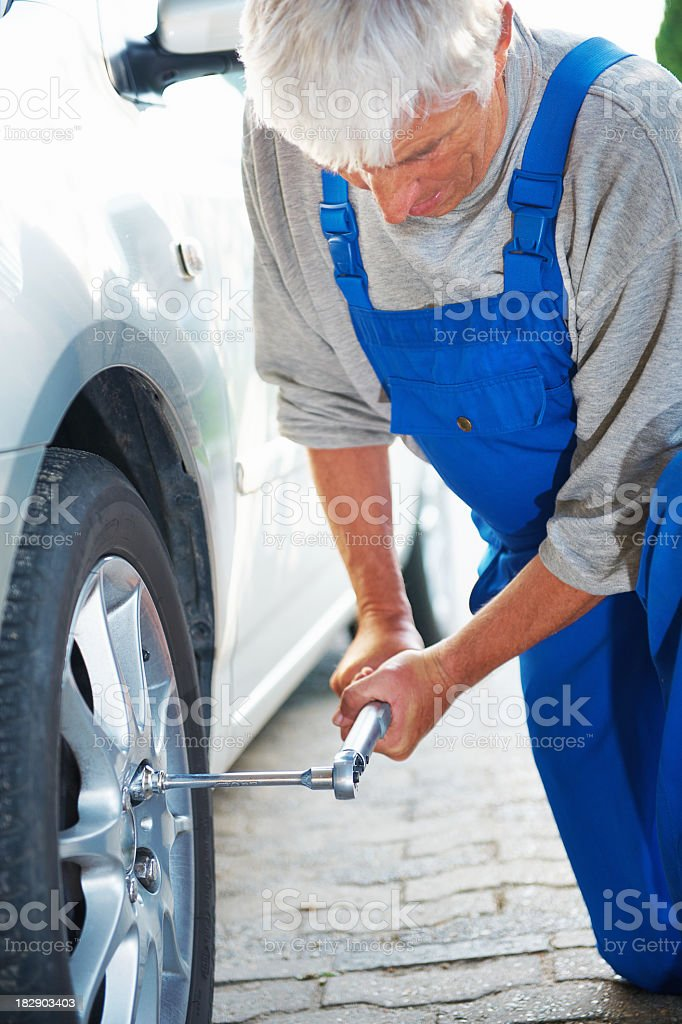 Handsome senior changing tire on his car royalty-free stock photo