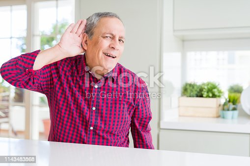1029343276istockphoto Handsome senior man at home smiling with hand over ear listening an hearing to rumor or gossip. Deafness concept. 1143483868