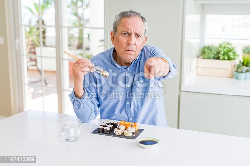 Handsome senior man eating take away sushi using chopsticks at home pointing with finger to the camera and to you, hand sign, positive and confident gesture from the front