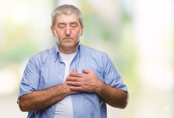 hübscher senior mann über isolierte hintergrund lächelnd mit händen auf brust mit geschlossenen augen und dankbar geste auf gesicht. gesundheitskonzept. - die wahrheit tut weh stock-fotos und bilder