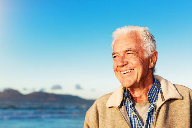 Handsome senior man relaxing in winter sunshine by the ocean stock photo