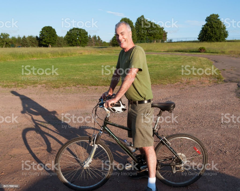 Handsome Senior Man Riding Bicycle in Countryside stock photo