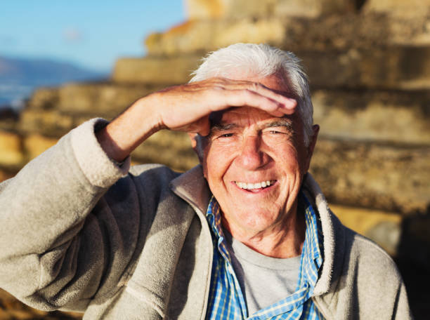 Handsome senior man shields his eyes against bright morning sun stock photo
