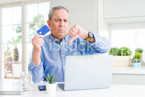 Handsome senior man shopping online using credit card and laptop at home with angry face, negative sign showing dislike with thumbs down, rejection concept