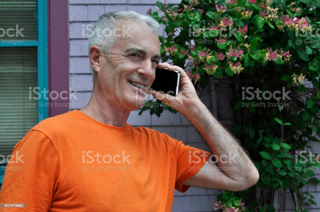 Handsome Senior Man Talking on Cell Phone in Colorful Setting stock photo