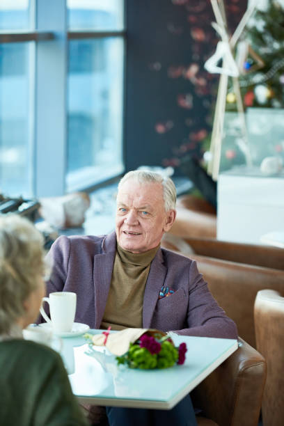 Handsome senior man talking to woman on date stock photo