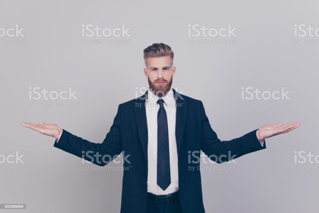Handsome serious attractive expert experienced qualified leader brutal pensive confident concentrated man wearing black suit with white shirt demonstrating empty blank place isolated gray background stock photo