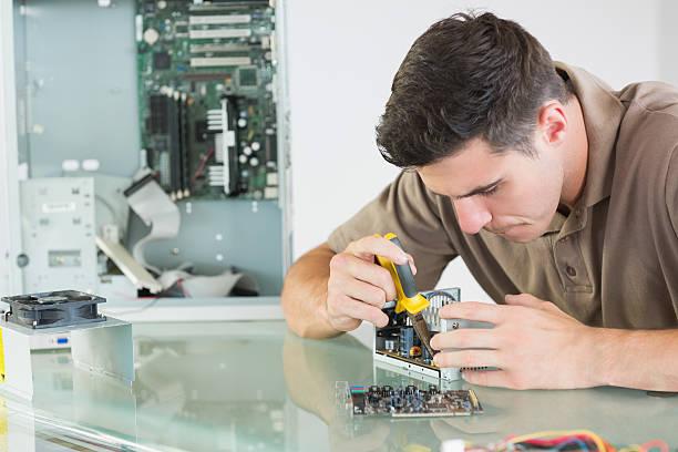 przystojny poważne inżynier komputera naprawa sprzętu z plier - człowiek maszyna zdjęcia i obrazy z banku zdjęć