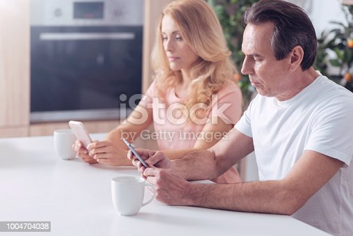 Problems in family. Handsome serious adult man sitting with his wife and paying no attention to her while being focused on his smartphone