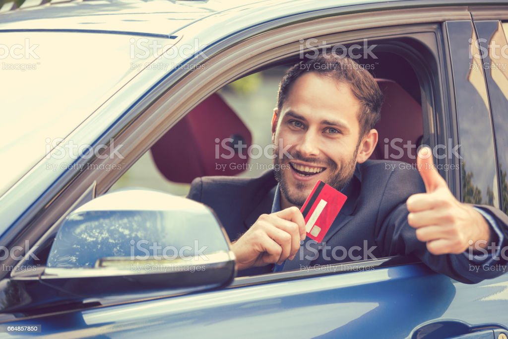 Handsome serious man driving a new car stock photo