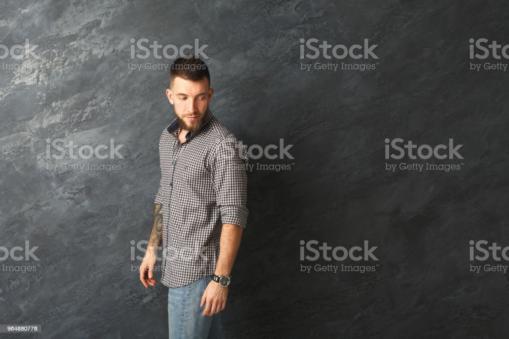 Handsome serious tattooed man looking back royalty-free stock photo