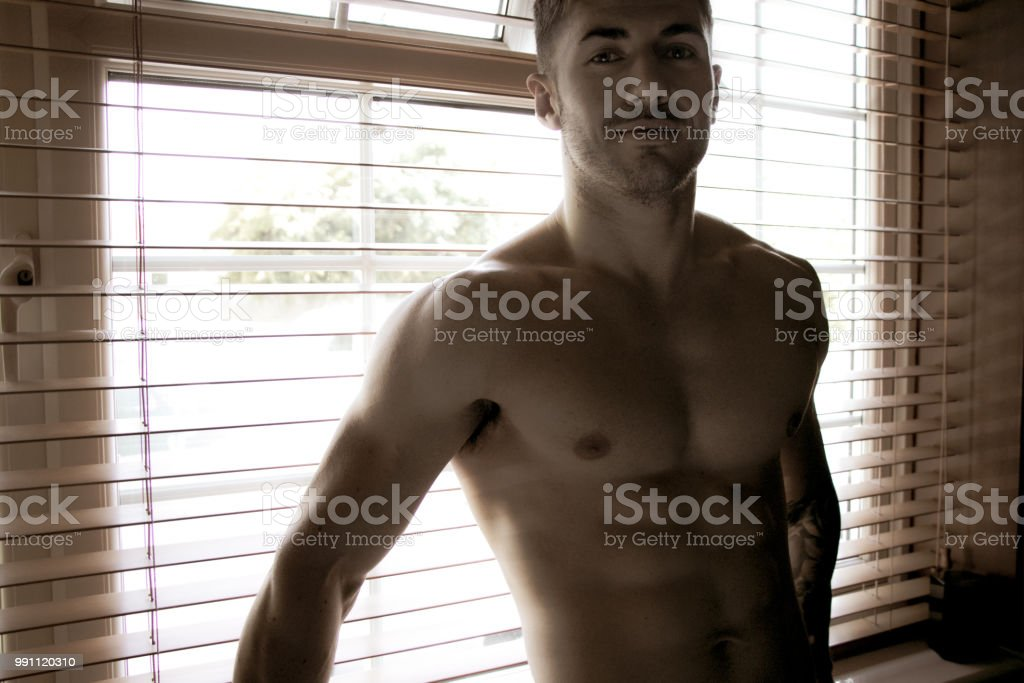 Handsome, sexy, topless, shirtless man stands in front of brown blinds and smiles at camera stock photo