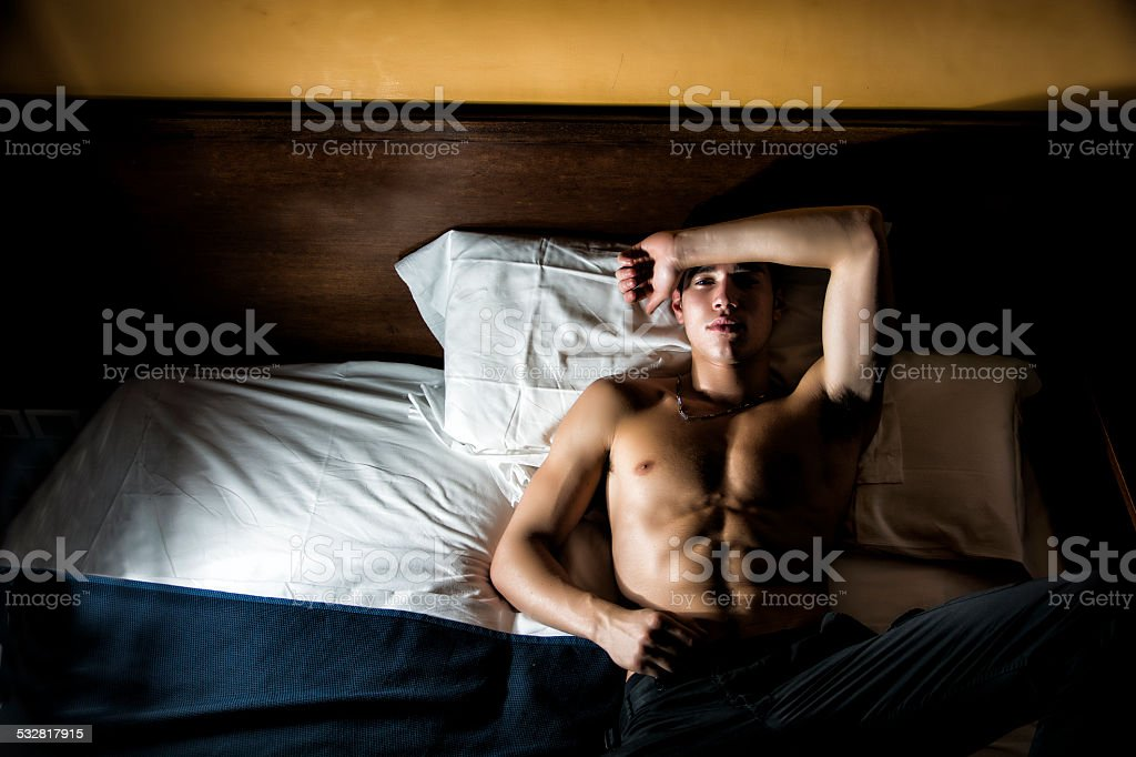 Handsome shirtless athletic young man in bed at night royalty-free stock photo