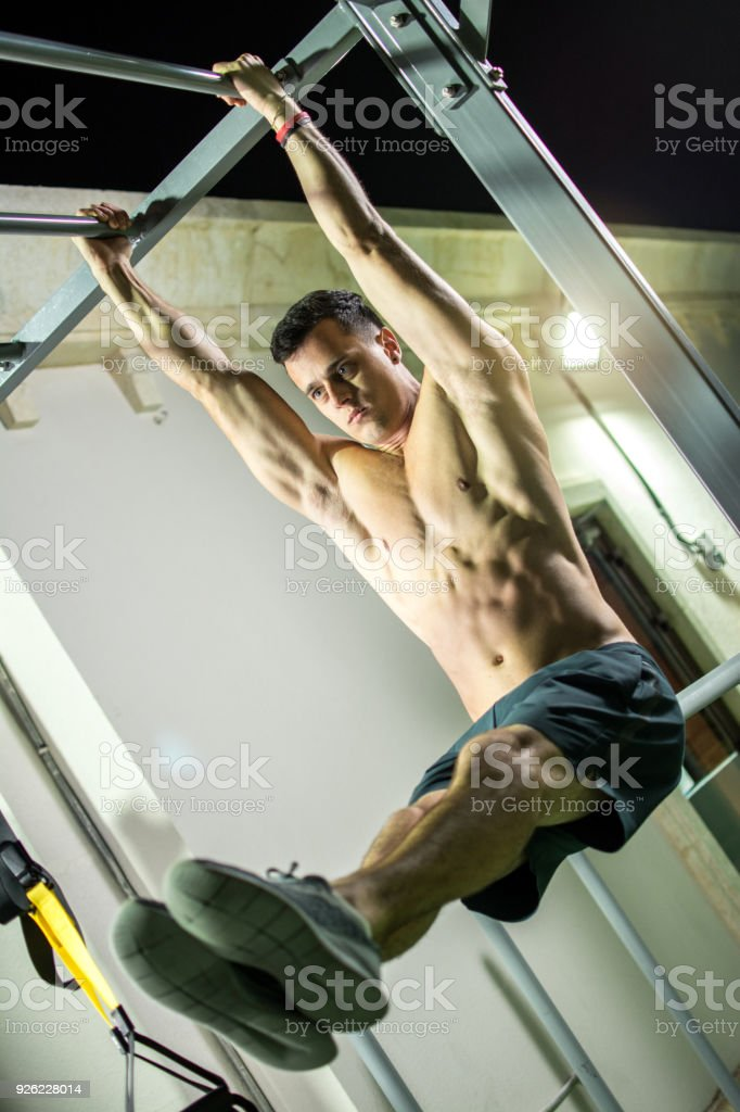 Handsome Shirtless Man Doing Pull Ups In The Lsit Position