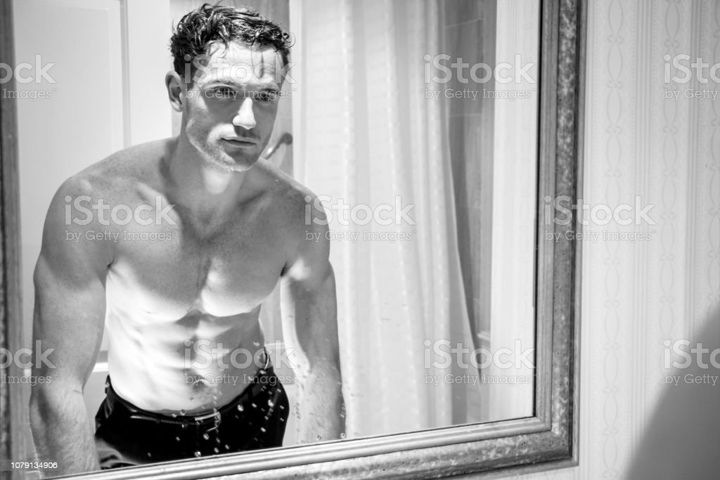 Handsome shirtless man with muscular body and sixpack abs looking at his reflection in bathroom mirror stock photo