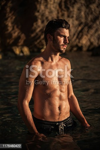 519676858 istock photo Handsome shirtless muscular fitness man at the beach, looking aside 1175460422