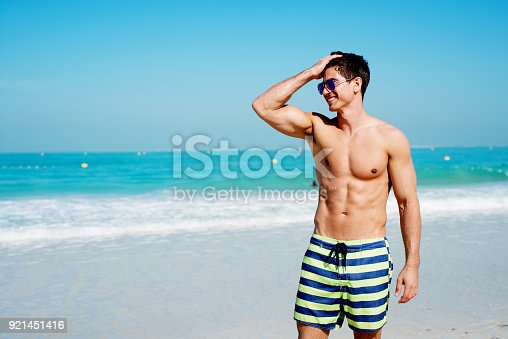 istock Handsome shirtless muscular fitness man at the beach, looking aside and smiling. 921451416