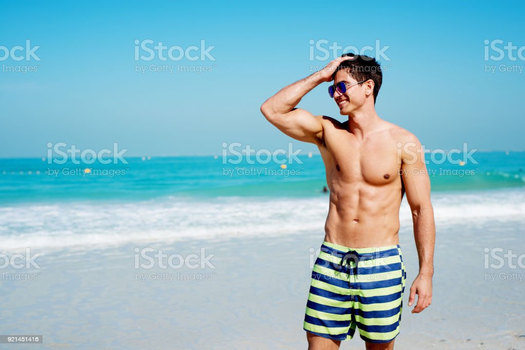 Handsome shirtless muscular fitness man at the beach, looking aside and smiling. stock photo
