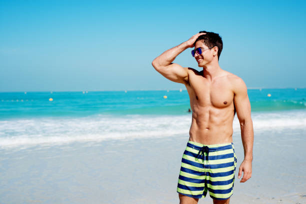Handsome shirtless muscular fitness man at the beach, looking aside and smiling. Handsome shirtless muscular fitness man at the beach, looking aside and smiling. abdominal muscle stock pictures, royalty-free photos & images