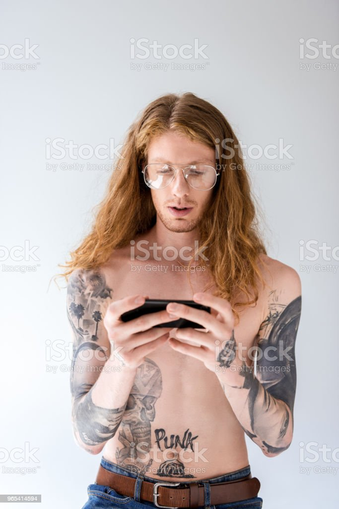 handsome shirtless tattooed man with curly hair looking at smartphone isolated on white zbiór zdjęć royalty-free