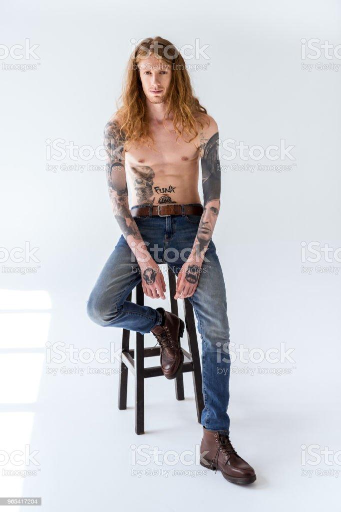 gut aussehend tätowiert nacktem Oberkörper Mann mit lockigem Haar auf Stuhl sitzend und Wegsehen auf weiß - Lizenzfrei Design Stock-Foto