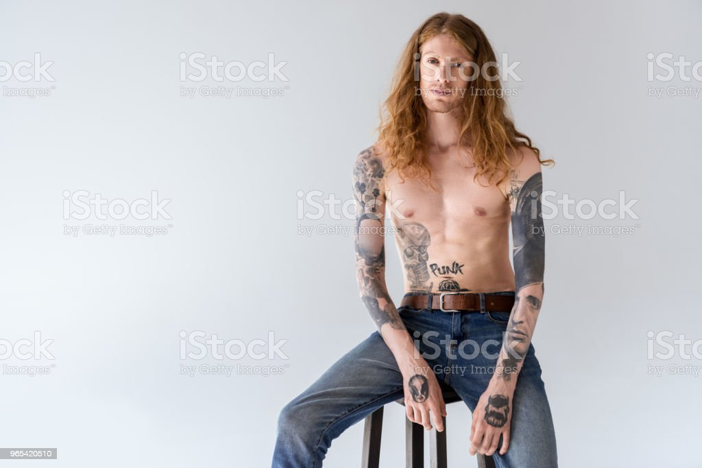 handsome shirtless tattooed man with curly hair sitting on chair and looking at camera isolated on white royalty-free stock photo
