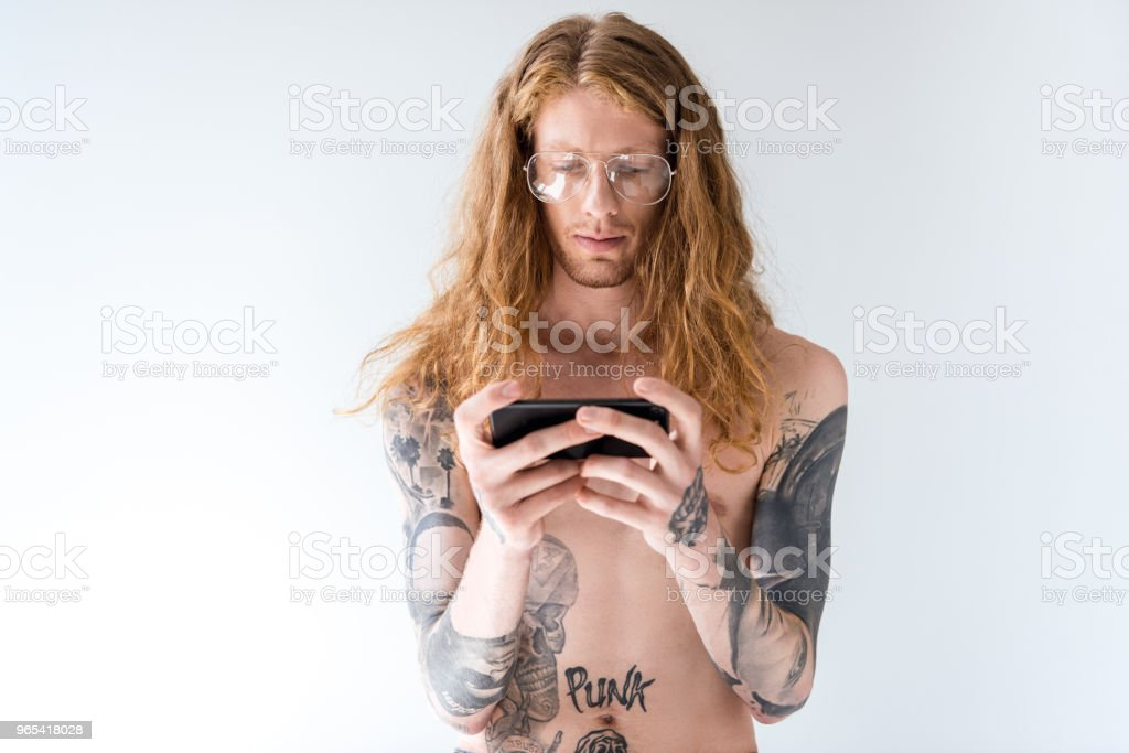 handsome shirtless tattooed man with curly hair using smartphone isolated on white royalty-free stock photo