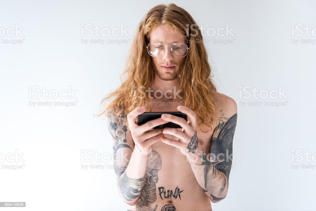 英俊的裸上身紋身男子捲曲的頭髮使用智慧手機隔離白色 - 免版稅一個人圖庫照片