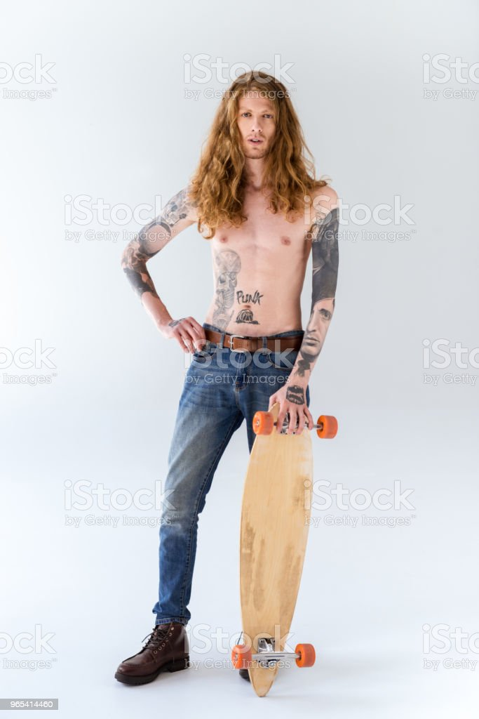 handsome shirtless tattooed sportsman with curly hair standing with longboard on white zbiór zdjęć royalty-free