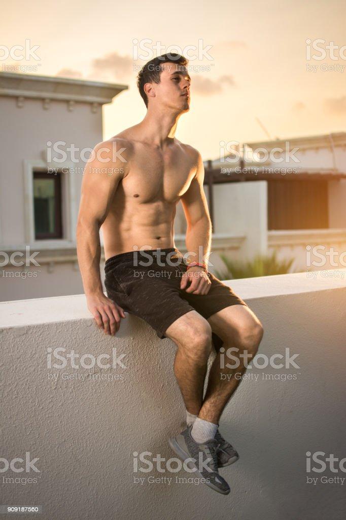 a8014788670b Guapo Sin Camisa Hombre Joven Sentado En La Pared En La Azotea Al ...