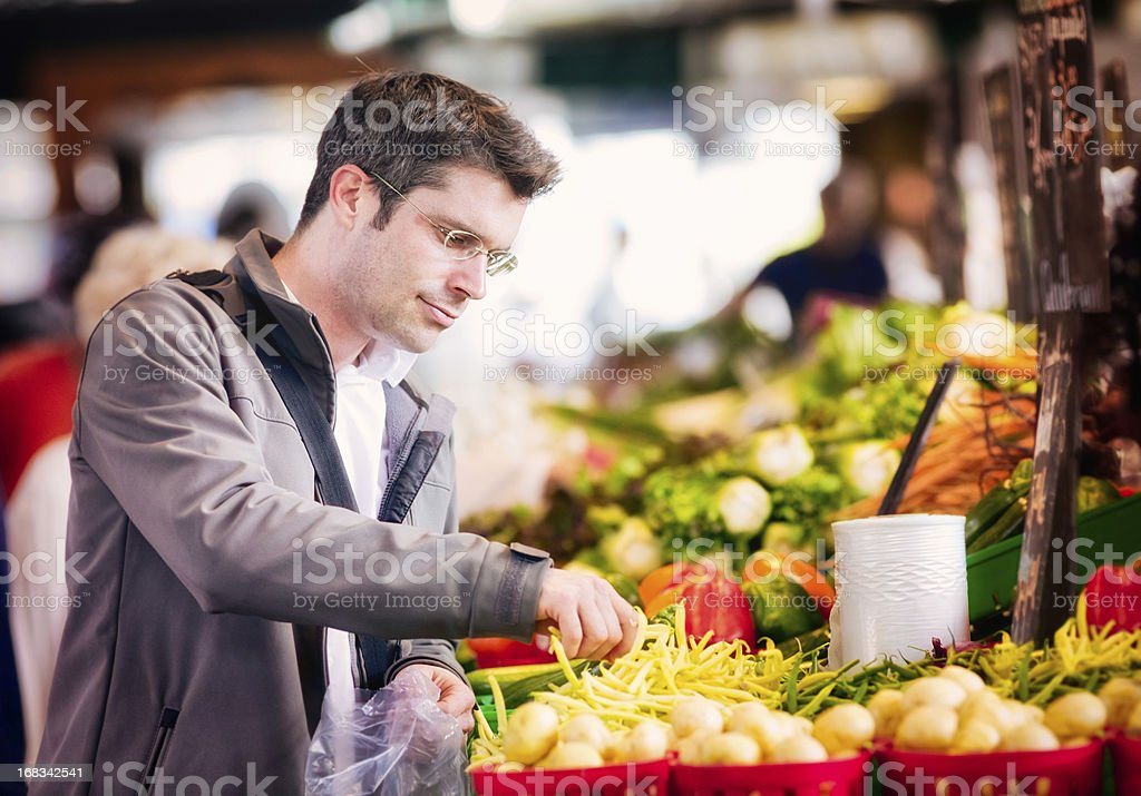 Handsome single man picking up string beans at market royalty-free stock photo