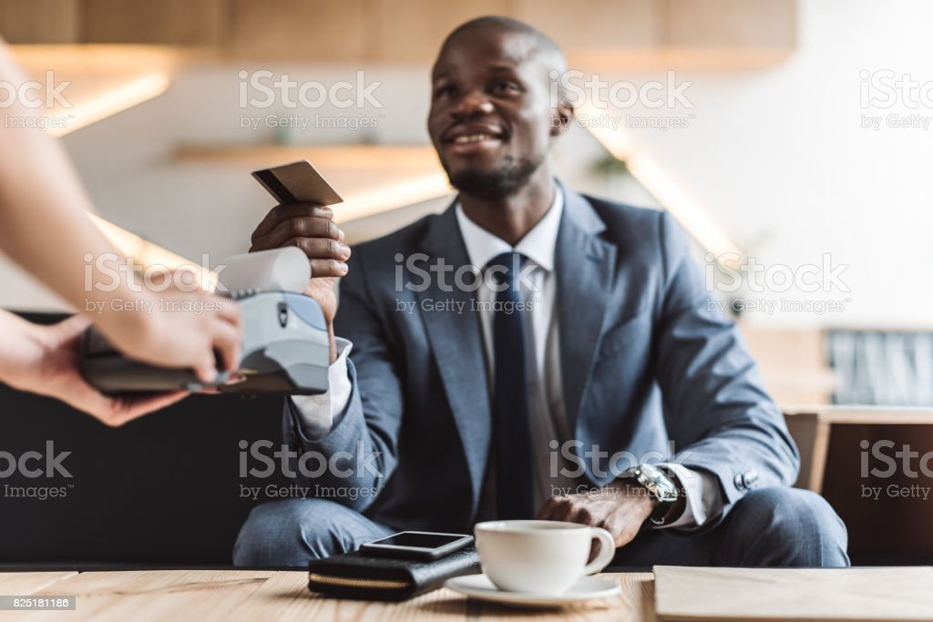 handsome smiling african american businessman paying with credit card in cafe stock photo