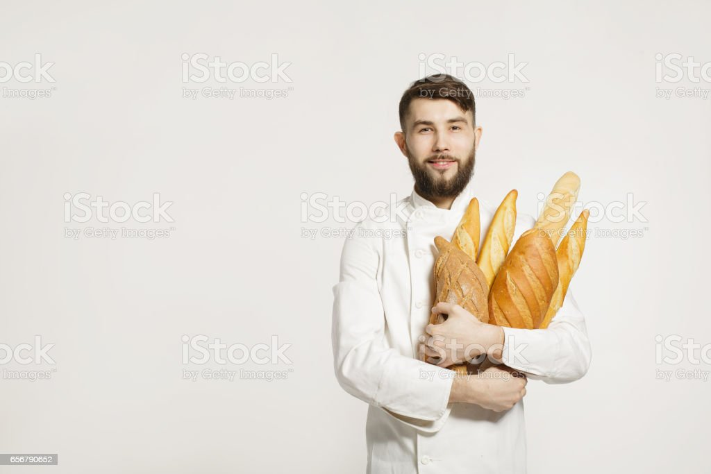 Handsome smiling baker in uniform holding baguettes with bread shelves on the white background. Handsome man holding warm bread in his hands on white background. - fotografia de stock