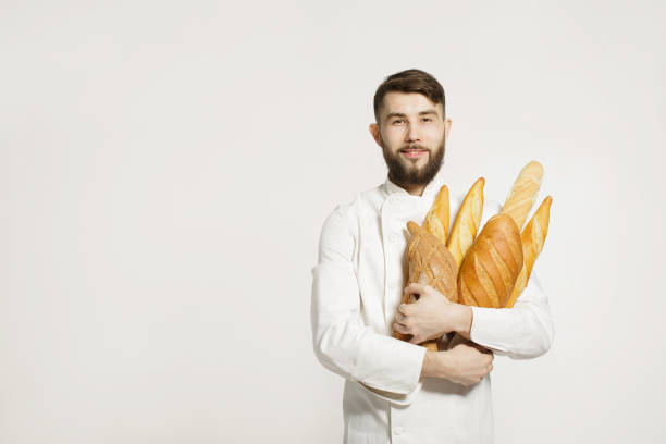 Handsome smiling baker in uniform holding baguettes with bread shelves on the white background. Handsome man holding warm bread in his hands on white background. stock photo