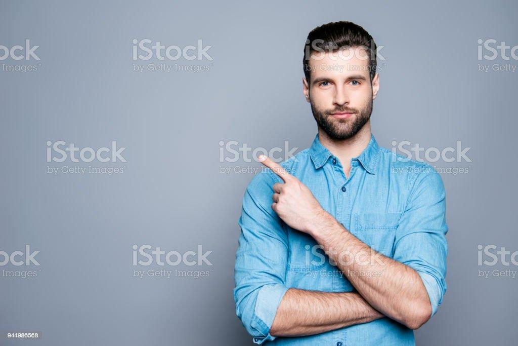 Sonriendo guapo barba hombre apuntando lejos sobre fondo gris foto de stock libre de derechos