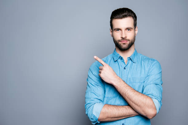 Handsome smiling bearded man pointing away on gray background stock photo
