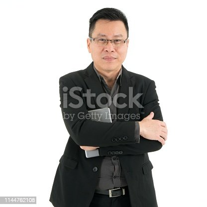 Handsome smiling business man in suite holding mobile device standing with crossed arms, isolated on white background