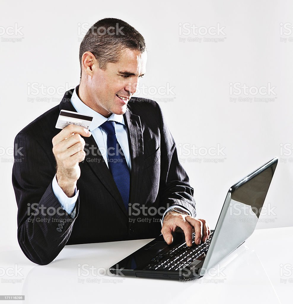 Handsome smiling businessman enjoys some online shopping royalty-free stock photo
