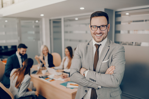 istock Handsome smiling businessman in formal wear and eyeglasses standing at boardroom with arms crossed. Love and respect do not automatically accompany a position of leadership. They must be earned 1140818577